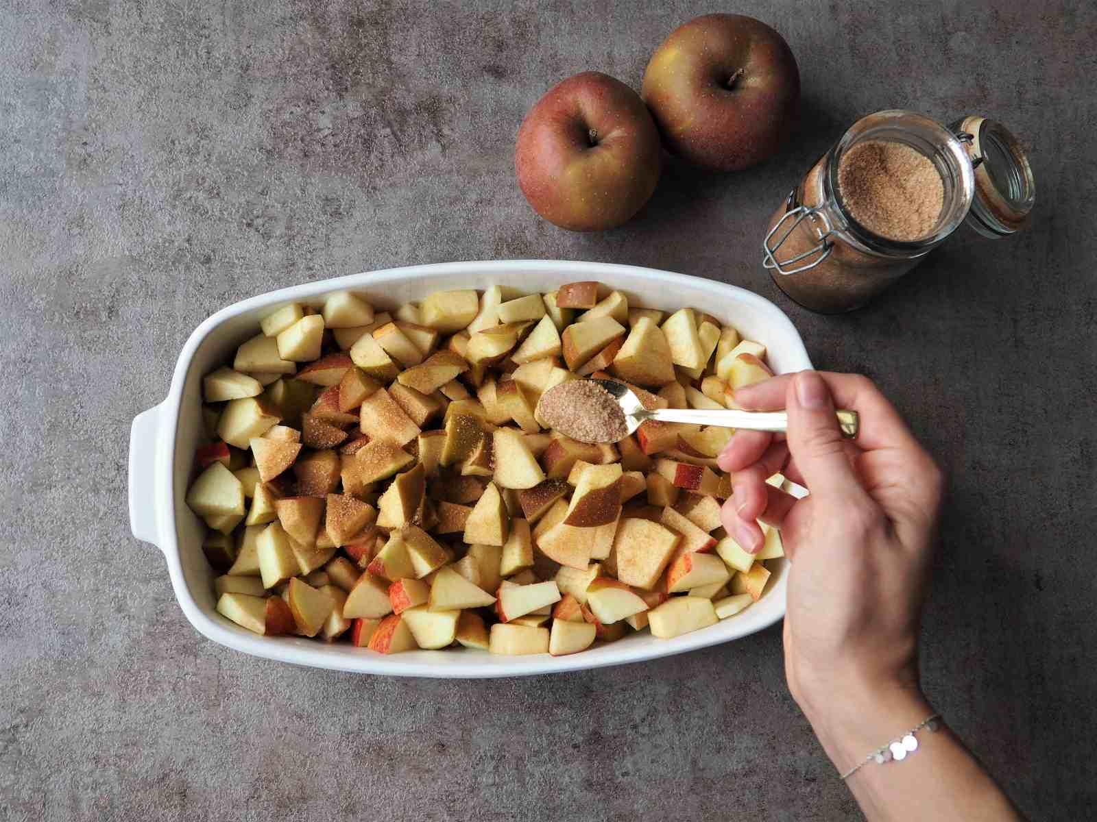 Gewürfelte Äpfel werden in Auflaufform mit Zimt-Zucker bestreut