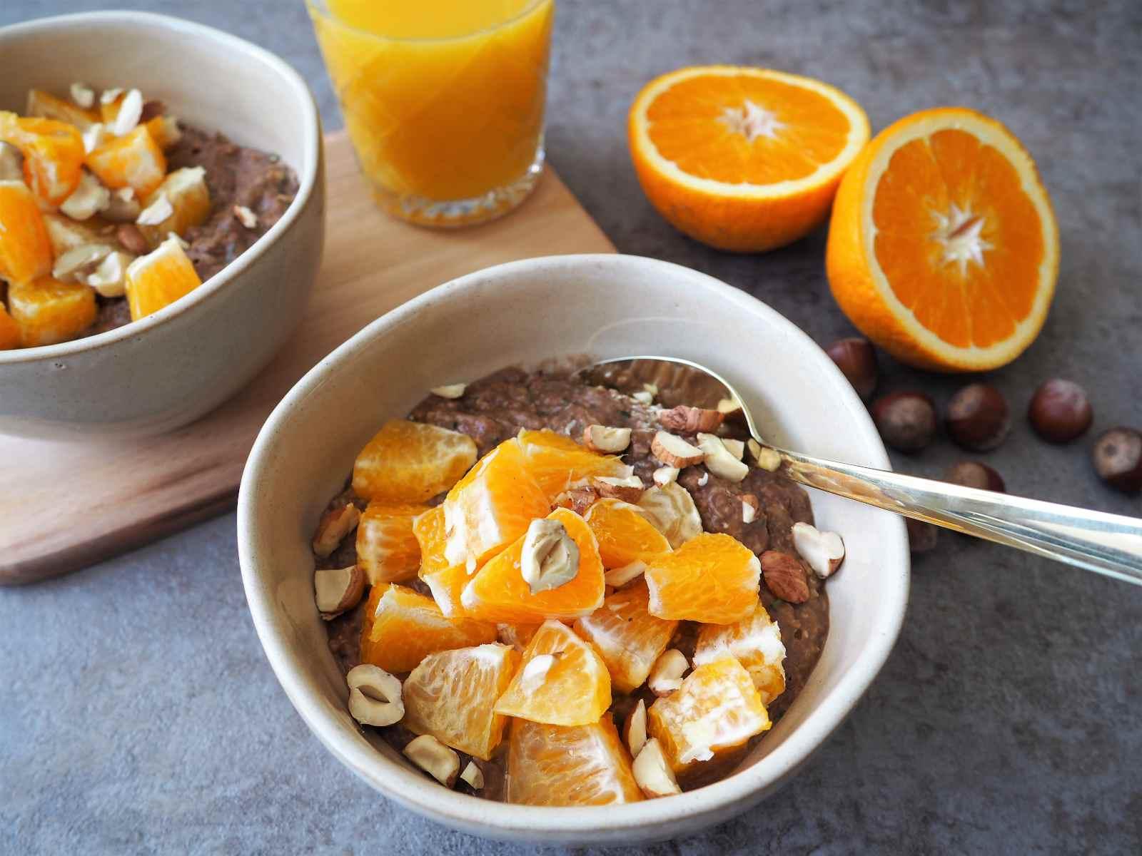 Schokoladiges Zucchini-Orangen-Porridge angerichtet mit Nüssen und Orangensaft