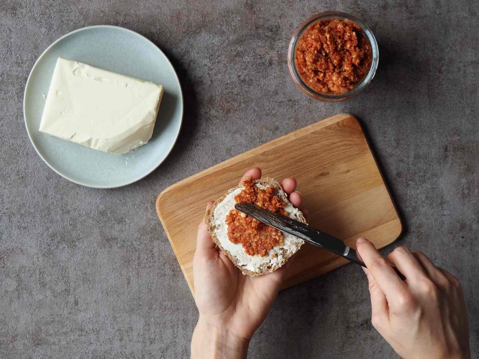 Veganer Brotaufstrich nach Mett-Art wird auf Brötchen geschmiert