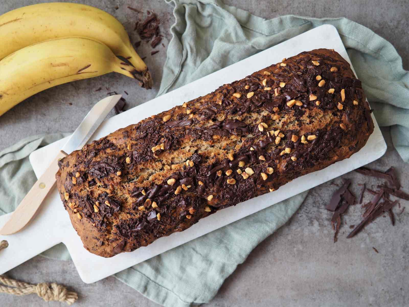 Bananenbrot mit Haselnüssen und Schokolade angerichtet auf Platte