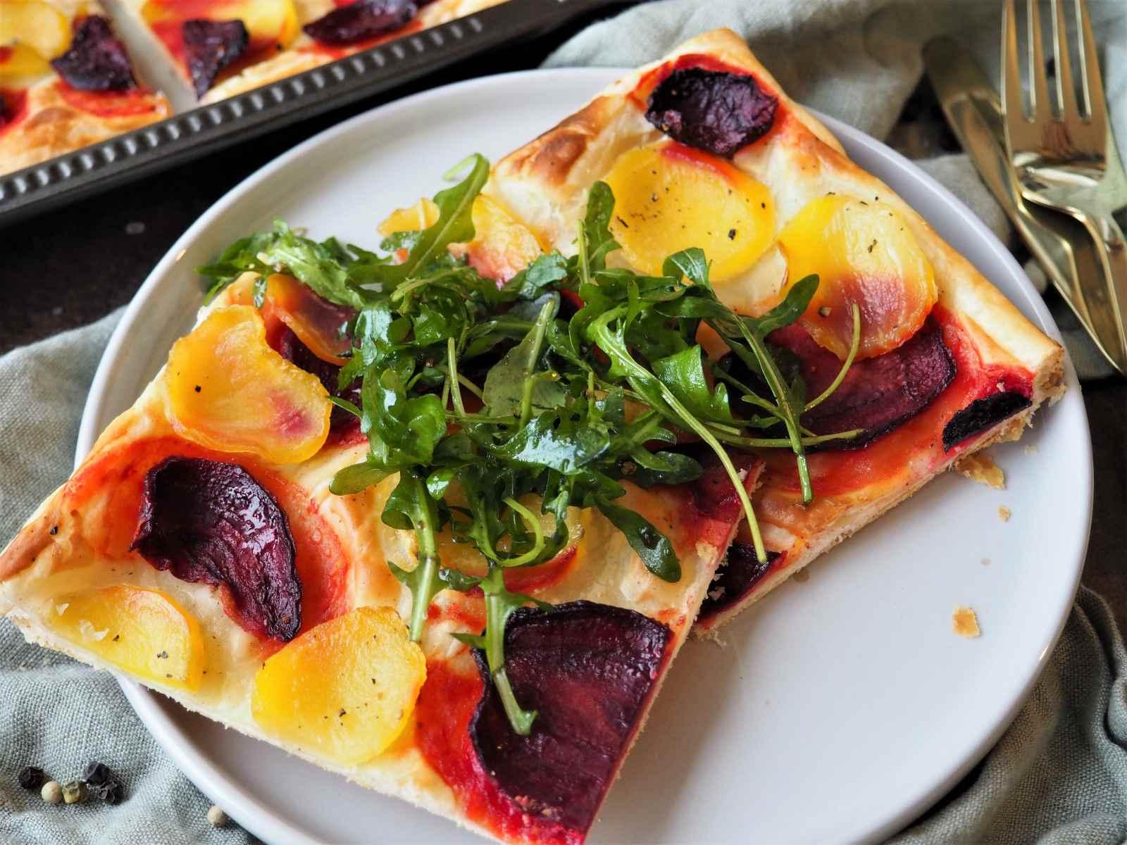 Vegane Blätterteigpizza mit Gelber und Roter Bete und Rucola-Garnitur Nahaufnahme