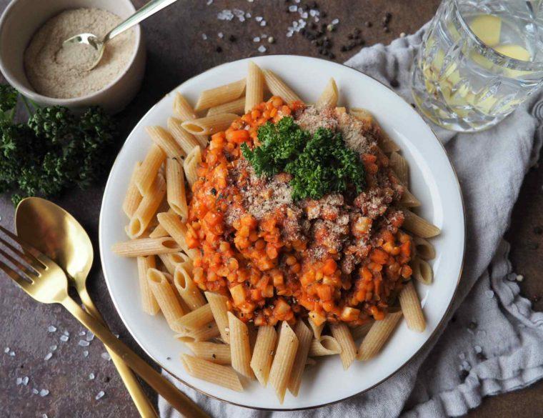 Vegane Linsenbolognese auf Vollkornnudeln mit Hefeflocken und Petersilie dazu ein Glas Wasser mit Ingwerscheiben