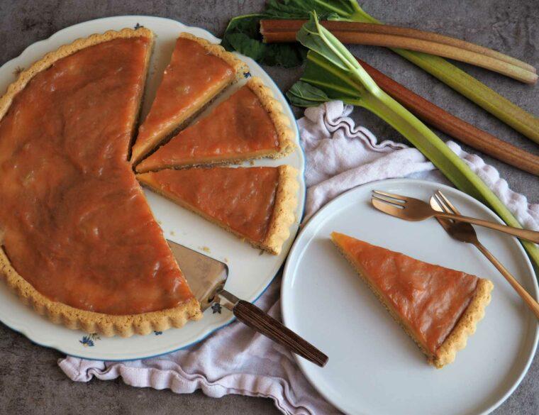 Veganer Rhabarberkuchen mit Pudding und Biskuitboden auf Tortenplatte