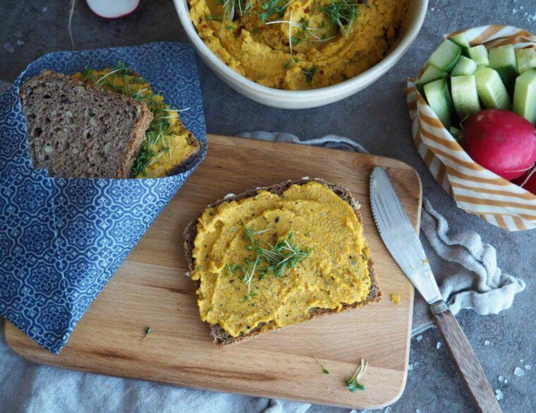 Möhren-Hummus auf eine Scheibe Brot geschmiert und mit Kresse dekoriert