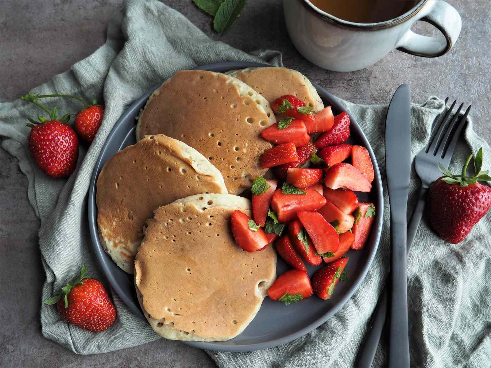 Vegane Pancakes mit Ahornsirup und Erdbeeren